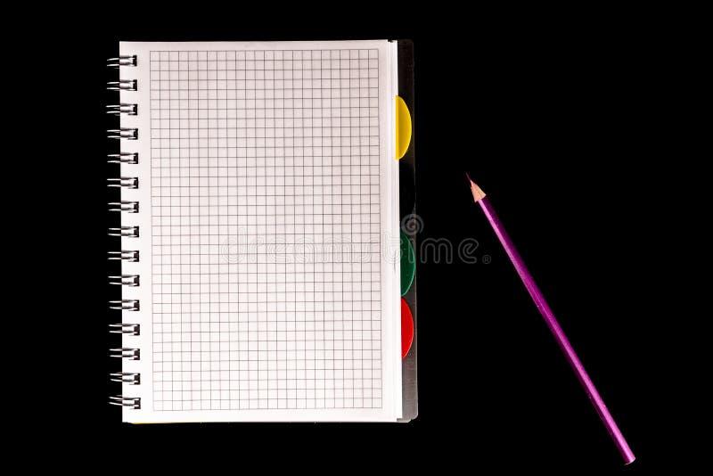 färgblyertspenna och anteckningsbok, isolat på svart bakgrund arkivbilder