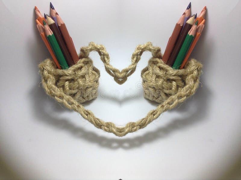 Färgblyertspennor i hållare för jutevirkningblyertspenna arkivfoton