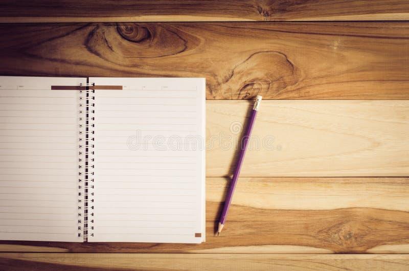 Färgblyertspennor i kopparna och anteckningsboken som förläggas på ett skrivbord royaltyfri fotografi