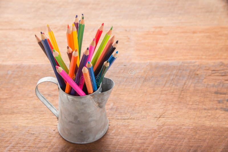 Färgblyertspennor i tenn kan, trätabellbakgrund books isolerat gammalt för begrepp utbildning royaltyfri foto