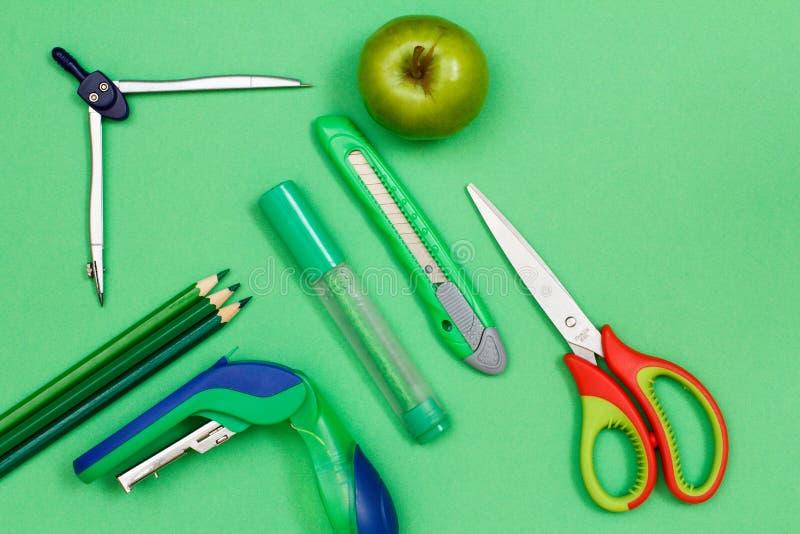 Färgblyertspennor, kompass, häftapparat, filtpenna, pappers- kniv, äpple royaltyfri bild