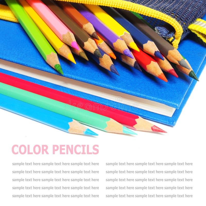 Färgblyertspennor och en bok för blå anmärkning som isoleras på vit fotografering för bildbyråer