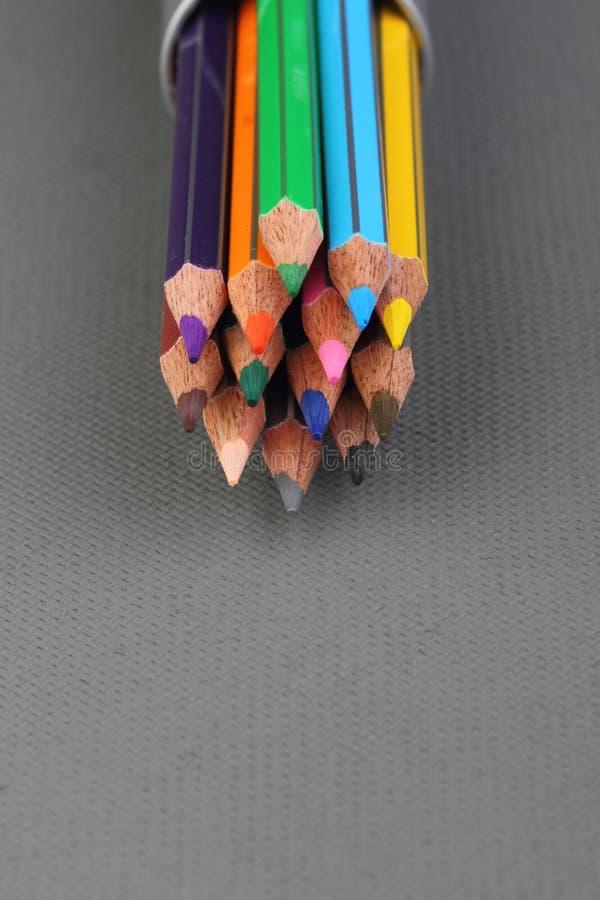 Färgblyertspennor på grå bakgrund arkivfoto