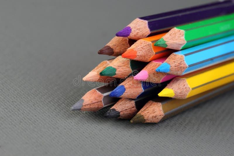 Färgblyertspennor på grå bakgrund arkivbilder