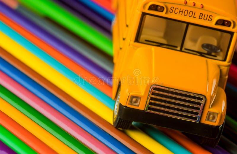 Färgblyertspennor på gula skolbussskolatillförsel fotografering för bildbyråer
