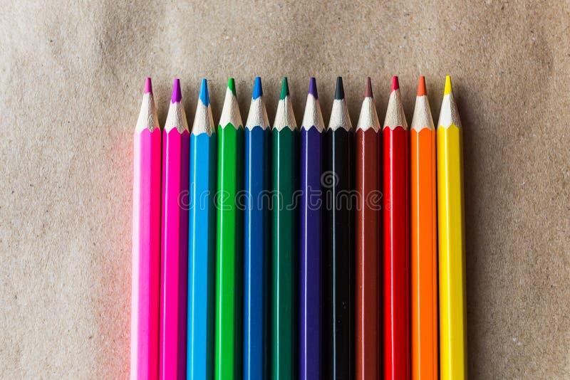 Färgblyertspennor på hemslöjdpapper arkivbild
