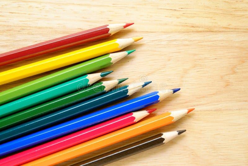 Färgblyertspennor på wood bakgrund arkivfoto