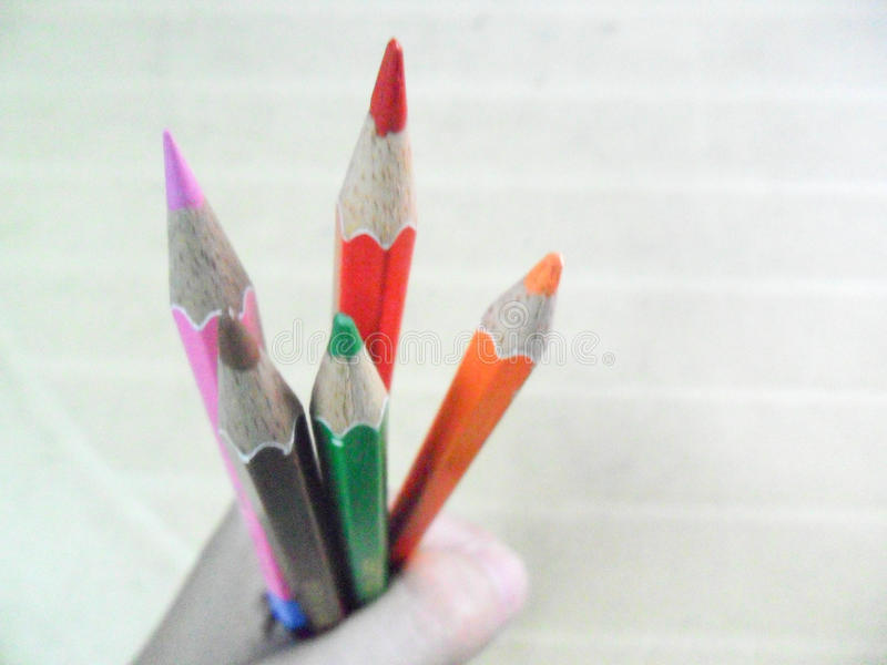 Färgblyertspennor som rymms av en enkel hand arkivbild
