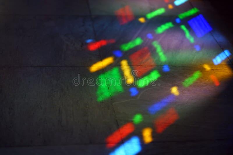 färger av ett målat glassfönster reflekterat på golvet royaltyfri foto