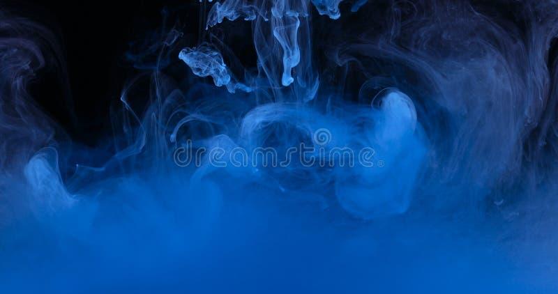 Färger för blått färgpulver i vatten som skapar vätskeArt Shapes fotografering för bildbyråer