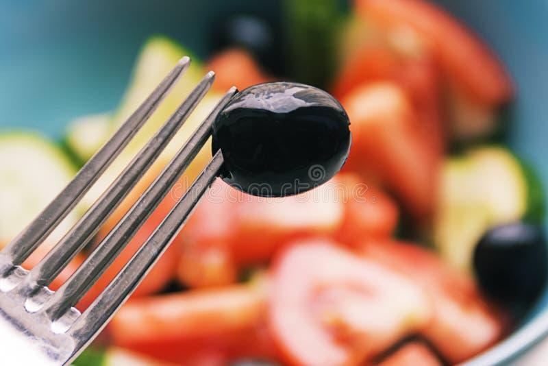 Färgfoto av salladgrönsaker på plattagaffel med oliv arkivbild