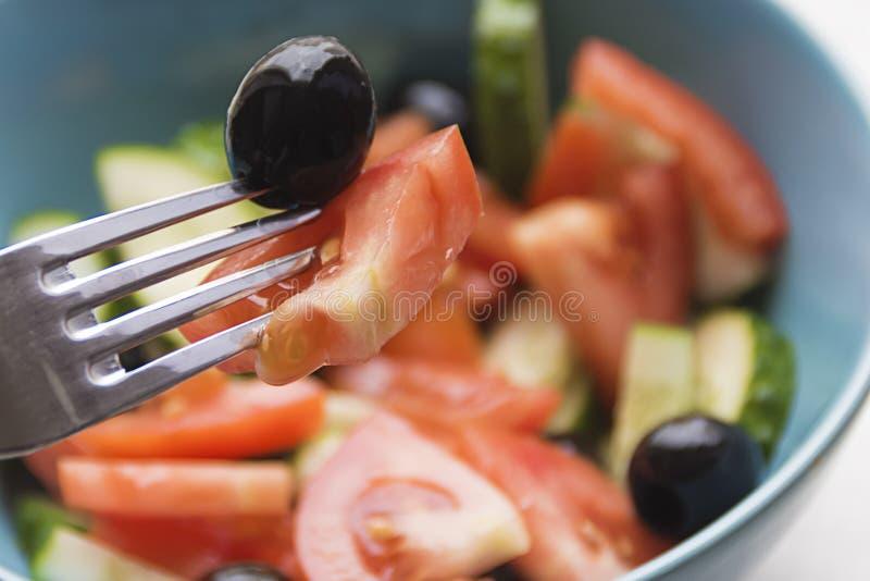 Färgfoto av salladgrönsaker på plattagaffel med oliv arkivfoto
