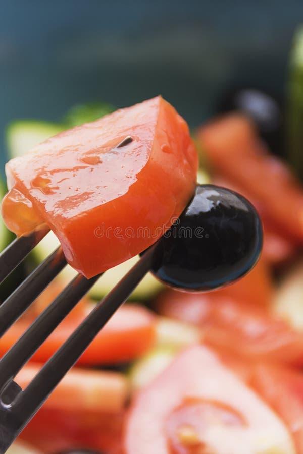 Färgfoto av salladgrönsaker på plattagaffel med oliv och tomaten fotografering för bildbyråer