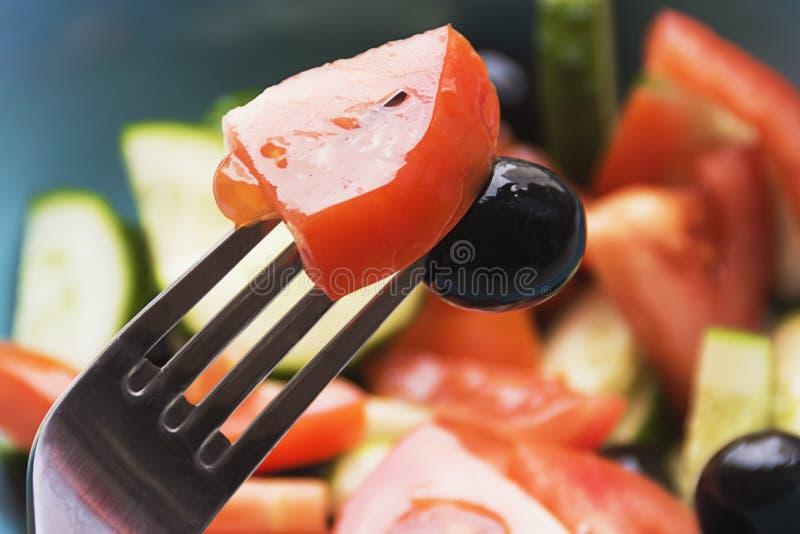 Färgfoto av salladgrönsaker på plattagaffel med oliv och tomaten arkivfoton