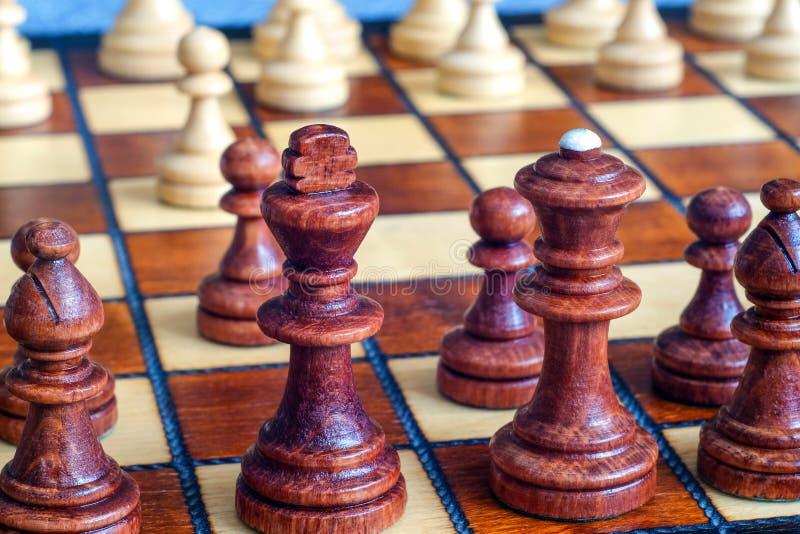 Färgfoto av schackbrädet och schackstycken, träschackstycken på schackbrädet Svartdiagram i förgrunden slapp fokus Bl royaltyfria bilder