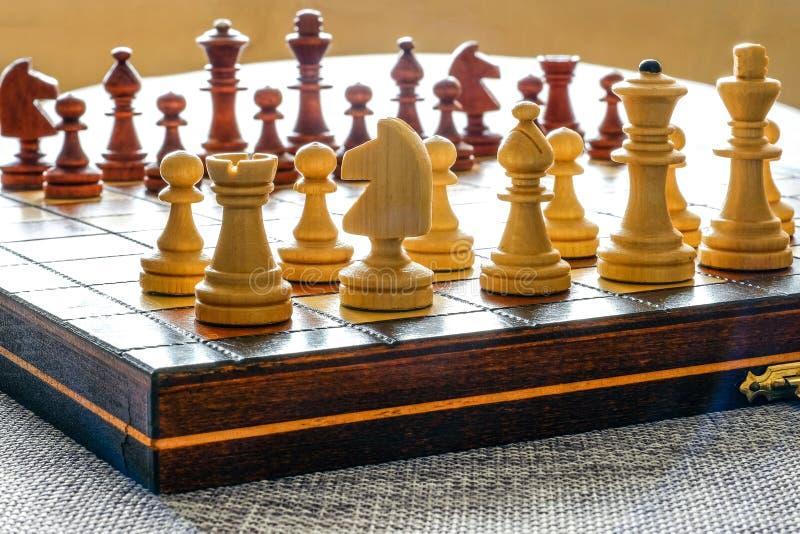 Färgfoto av schackbrädet och schackstycken, träschackstycken på schackbrädet Vitdiagram i förgrunden slappt arkivfoto