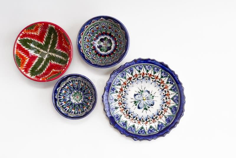 Färgfulla ostkeramiska plattor och skålar med nationellt mönster i blå och röd färg isolerade på vit bakgrund, Taskent. royaltyfria foton