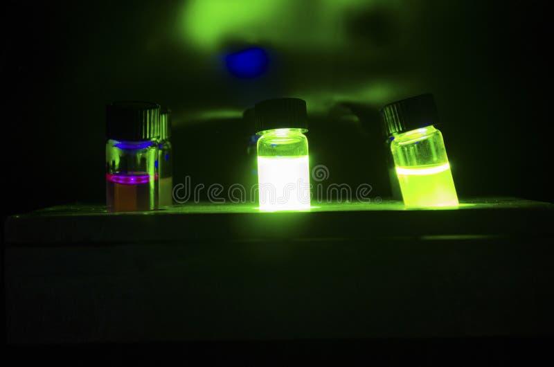 Färgglad ljus framkallad fotokemisk reaktion för katalysator i exponeringsglassmå medicinflaskor under klartecken i ett mörkt kem royaltyfri bild