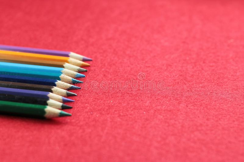Färgglad pensil med röd bakgrund arkivfoton
