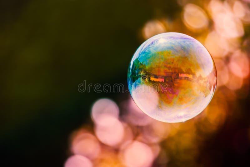 Färgglad såpbubbla som svävar mot en främst mörk bakgrund med en strimma av ljus bubblabokeh arkivfoto