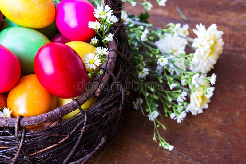 Färgglada easter ägg i brun korg royaltyfria bilder