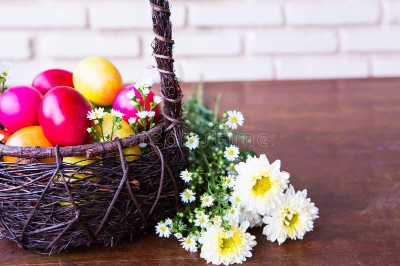 Färgglada easter ägg i brun korg arkivfoton