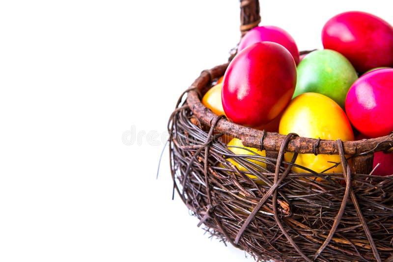Färgglada easter ägg i brun korg royaltyfri bild