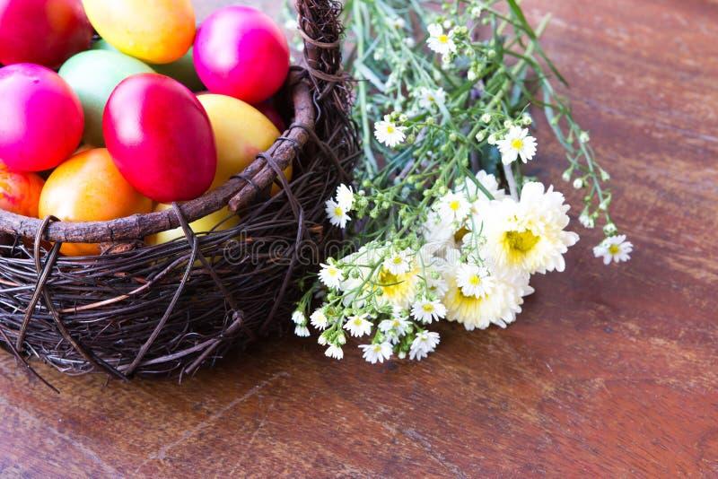 Färgglada easter ägg i brun korg fotografering för bildbyråer