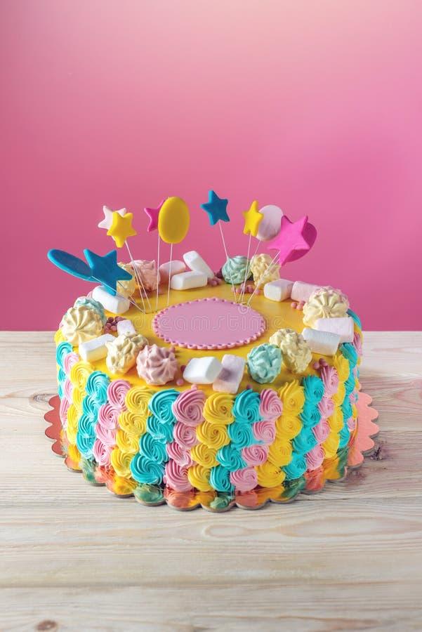 Färgglade barns kaka dekorerade med marshmallower och marängar arkivbild