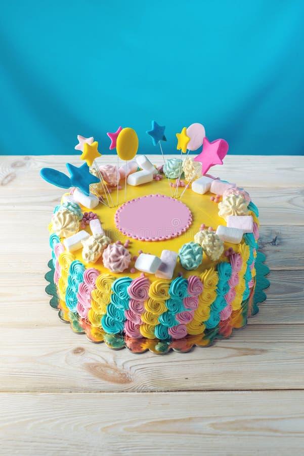 Färgglade barns kaka dekorerade med marshmallower och marängar royaltyfri bild