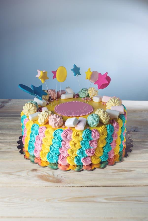 Färgglade barns kaka dekorerade med marshmallower och marängar arkivfoton