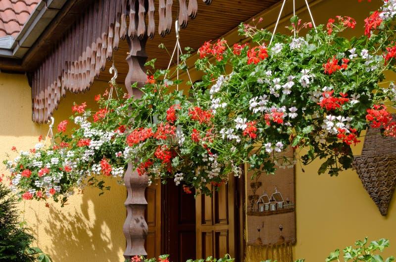 Färgglade blommakorgar som hänger på en farstubro arkivbild