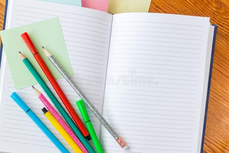 Färgglade blyertspennor och tuschpennor på den fodrade anteckningsboken royaltyfri bild
