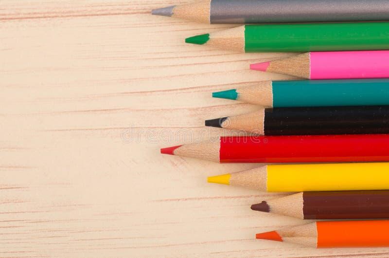 Färgglade blyertspennor på träskrivbordet för baksida till skolabegreppet royaltyfri fotografi