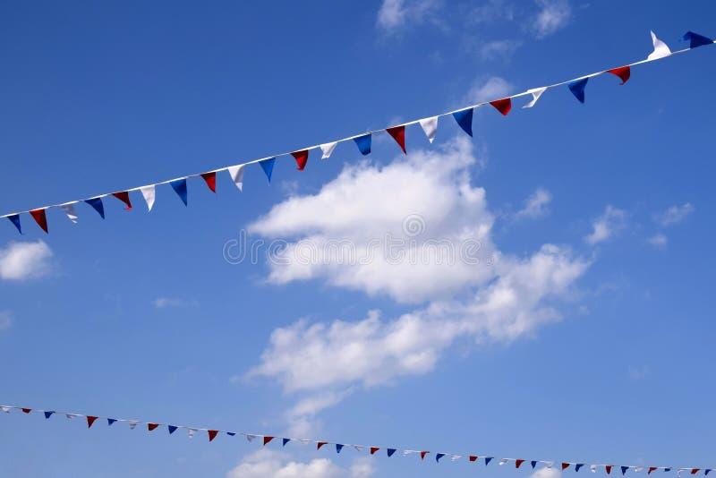 Färgglade dekorativa triangulära flaggor under blå himmel med moln fotografering för bildbyråer