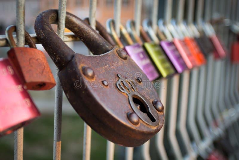 Färgglade förälskelsehänglås stängde sig till räcket på den Eiserner Steg bron i Regensburg, Tyskland royaltyfri fotografi