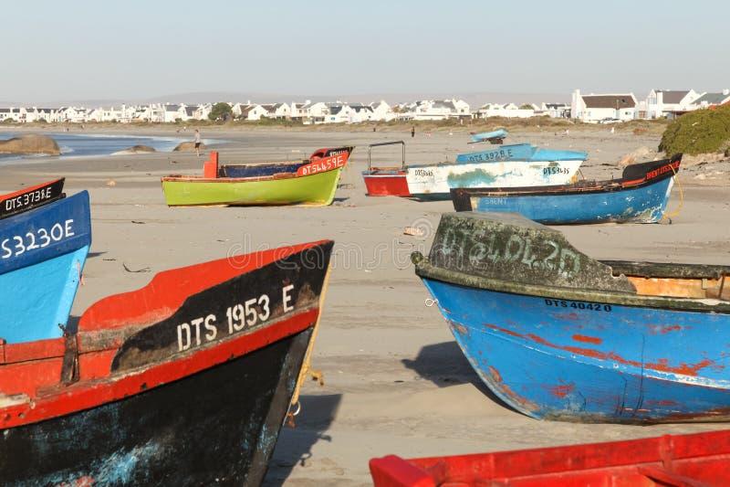 Färgglade fiskebåtar på stranden på Fadervår, litet fiskeläge med gourmet- restauranger på västkusten av Sydafrika royaltyfri fotografi
