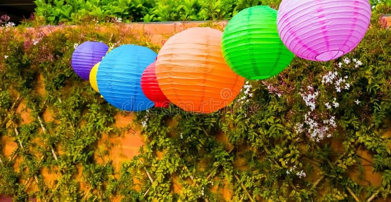 Färgglade kinesiska lyktor som hänger i en trädgård royaltyfri bild