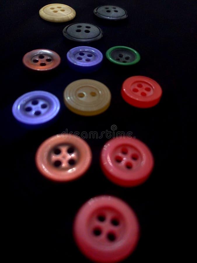 F?rgglade knappar p? svart bakgrund royaltyfri bild