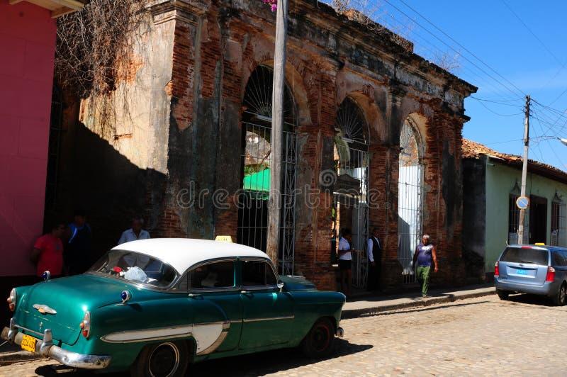 F?rgglade kontraster i Trinidad-stad med ruttna koloniala byggnader och oldtimerbilar royaltyfri fotografi