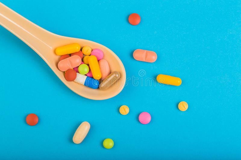 Färgglade medicinska piller på skeden och kapslar eller tillägg för terapi i bakgrund, begrepp av behandling och hälsovård royaltyfri bild