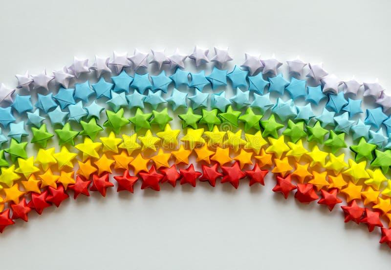 Färgglade origamistjärnor som bildar en regnbågebakgrund vektor illustrationer