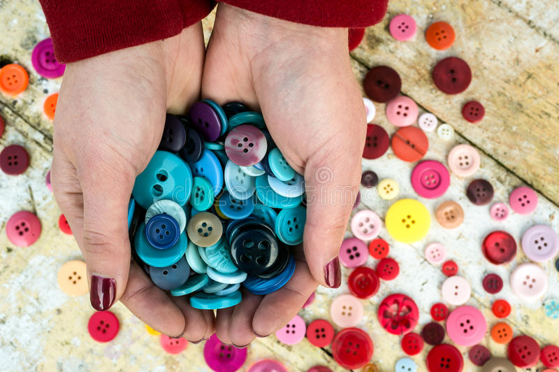 Färgglade sömnadknappar för hållande handfull arkivfoto