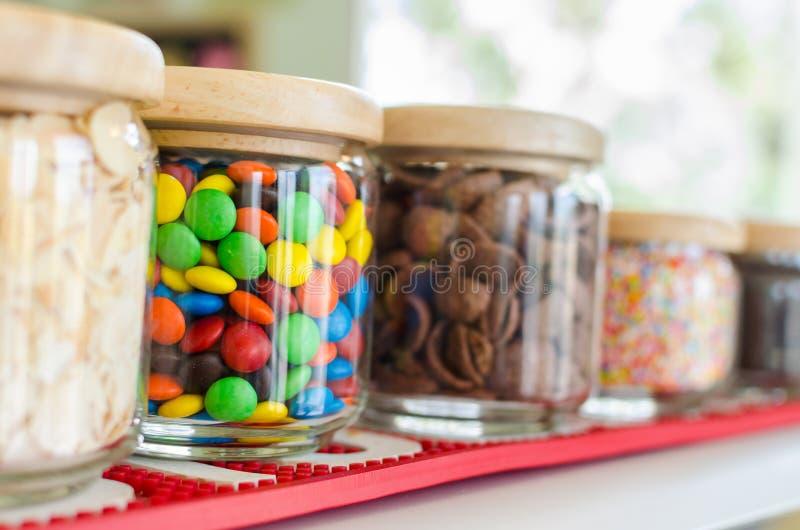 Färgglade söta godisar i flaska på hylla i efterrättlager fotografering för bildbyråer