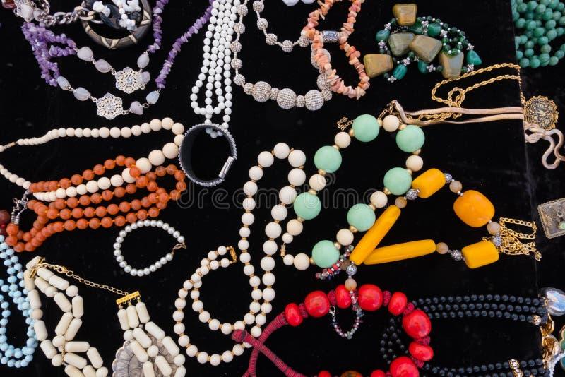 Färgglade smycken för stilfullt mode med svart sammetbakgrund fotografering för bildbyråer