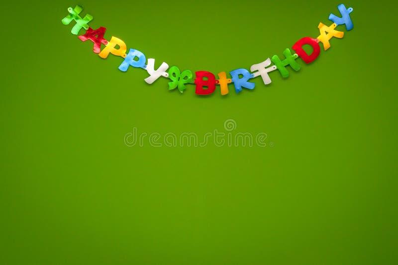 Färgglat hälsningbaner för lycklig födelsedag på en grön vägg i ett beröm- och partibegrepp arkivbilder