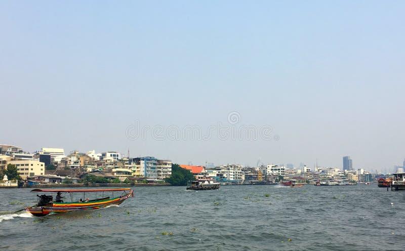 Färgglat thailändskt lång-svans sightfartyg på Chao Phraya River med cityscapebakgrund i blåsig och molnig dag royaltyfri bild