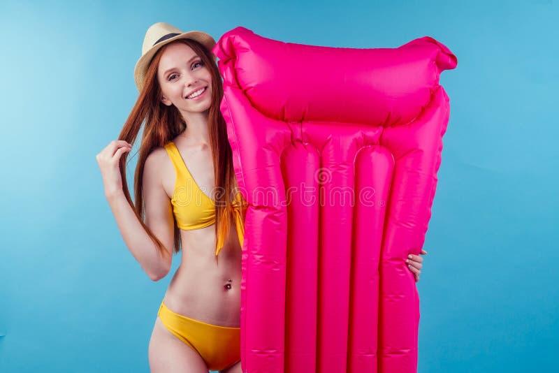 Färgingefära hona med gott utseende, snylt gul svimmingdräkt med uppblåsbar rosa madrass i studio blå royaltyfri fotografi
