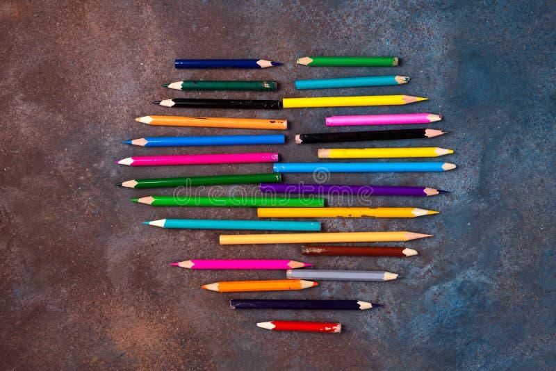 Färgpennahjärta - hjärtaform som göras av kulöra blyertspennor på stenbakgrund valentin för dag s arkivfoto