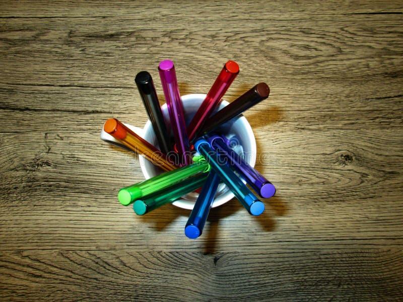 Färgpennor i en keramisk kopp royaltyfria bilder